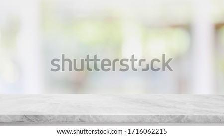 Empty white marble stone table top and blur glass window interior cafe and restaurant banner mock up abstract background - can used for display or montage your products. Royalty-Free Stock Photo #1716062215