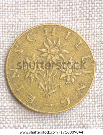 Hi resolution close up macro shot of a vintage gold coin on a fabric background flowers