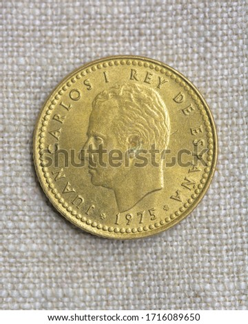 Hi resolution close up macro shot of a vintage golden coin on a fabric background head 1975 Spain