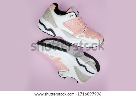 Pair of fashion colorful sneaker shoe on a pink isolated background Fitness sneakers shoes for training, running shoe. Sport shoes. Fashion pink sneaker, daddy shoe, ugly shoe, street fashion. #1716097996