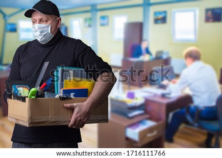 The masked man leaves the workplace. Dismissal from work. Job loss. Reduction of the company's staff. Unemployment. The shock of losing your job. An increase in the number of unemployed. Royalty-Free Stock Photo #1716111766