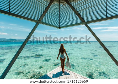 Luxury overwater bungalows Maldives resort woman going snorkeling from private hotel room island.  Travel vacation.  Aqua menthe trendy color of the new year 2020 #1716125659