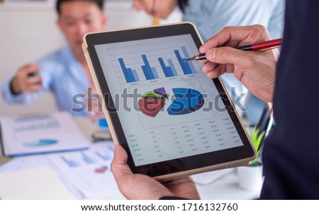 businessman pointing to the data on the tablet. The business team of the organization is brainstorming with charts and examining and analyzing the company's marketing and investments in the future. Royalty-Free Stock Photo #1716132760