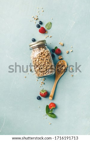 Home granola in a glass jar on blue concrete background Royalty-Free Stock Photo #1716191713