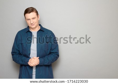 Studio portrait of confident satisfied man wearing casual blue shirt, smiling slightly, holding hands folded together, listening or waiting somebody, standing over gray background, copy space on right #1716223030