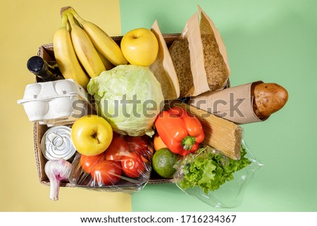 Top view of cardboard box with fresh food products on green-yellow background. Safe delivery. Contactless home food delivery during covid-19 quarantine. Food donation. Stock for rainy day. Top view.
