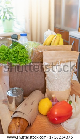 Fresh food products in cardboard box and on wooden table in kitchen interior. Safe delivery. Food donation. Contactless home delivery during pandemic. Stock for rainy day. Vertical photo. Soft focus.