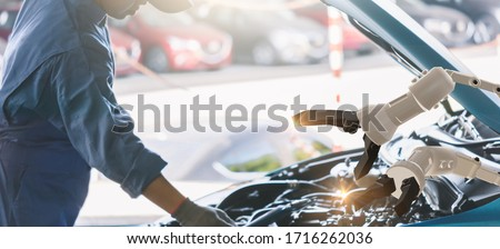 Asian Man mechanic inspection engine with hand robot ai machine.Blue car for service maintenance insurance with car engine.for transport automobile automotive ai. #1716262036