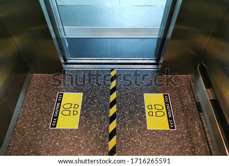 Selective focus to floor of passenger lift with standing marker for social distancing to avoid spreading coronavirus ( Covid-19 ). Location or distance concept. Idea for COVID-19 outbreak.
