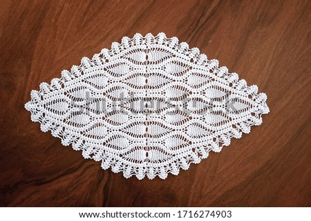 lace hand-knitted. lace tablecloth. Patterns knitted with lace crochet. Lace hand-knitted on wooden table. #1716274903