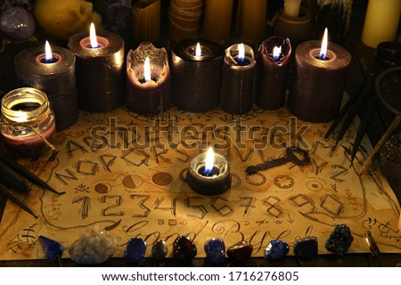 Talking spiritual board with black candles and old key. Wicca, esoteric and occult background with vintage magic objects for mystic rituals. Halloween and gothic concept #1716276805
