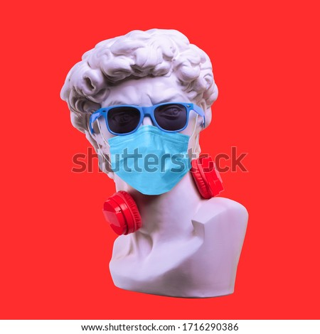 Statue. Earphone on a red background. Gypsum statue of David's head. Creative. Plaster statue of David's head in sunglasses and medical mask. Minimal concept art. #1716290386