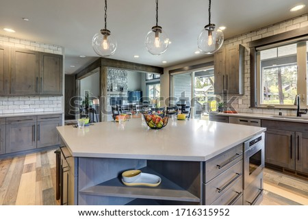 Absolutly stunning kitchen interior with grey tone of brown muted natural tones with light hardwood and rustic modern island with colorful plates. #1716315952