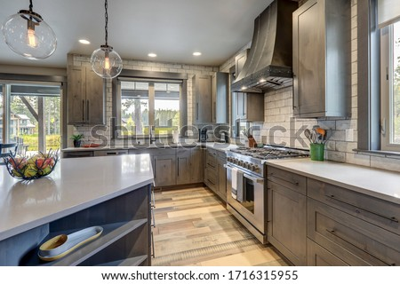 Absolutly stunning kitchen interior with grey tone of brown muted natural tones with light hardwood and rustic modern island with colorful plates. #1716315955