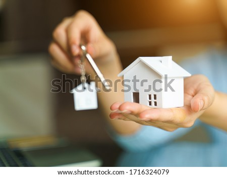 Woman holding white house model and house key in hand.Mortgage loan approval  home loan and insurance concept. #1716324079