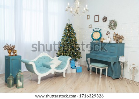 Blue sofa and piano in a beautiful classic interior with Christmas decorations. Gold and blue balloons on the Christmas tree with gift boxes. Blue and gold decoration of the new year home interior