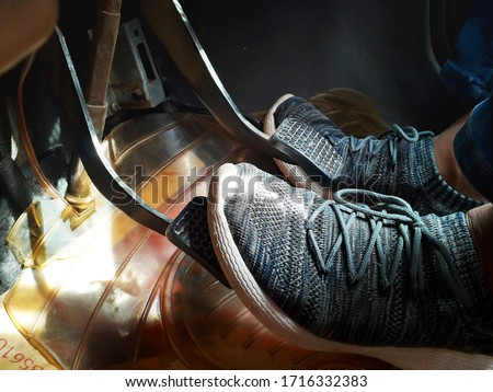 An Asian man is driving Indian car and his feet are on accelerator, brake and clutch / feet in car in nice shoes Royalty-Free Stock Photo #1716332383