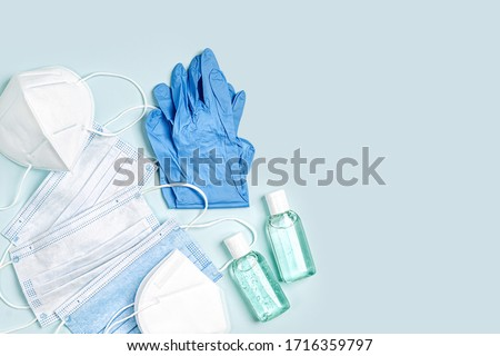 White medical masks and respirators with glove, hand sanitizer on blue background.  Face mask protection  KN95 or N95 and surgical masks for protection virus, flu, coronavirus, COVID-19.   #1716359797