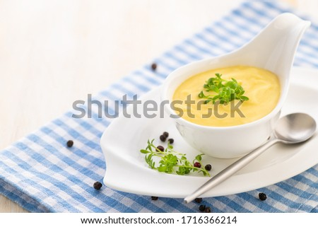 Hollandaise sauce. Classic French cuisine sauce. Emulsion sauce of butter and egg yolks with vinegar. Served in a gravy boat on a blue napkin. Close-up. #1716366214