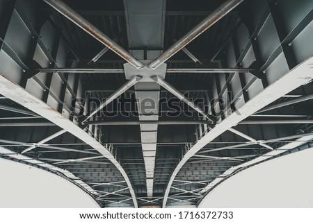 Metal structures under the bridge, large metal bridge over water Royalty-Free Stock Photo #1716372733
