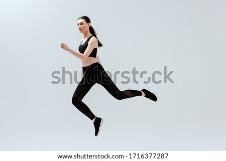 pretty woman in black sportswear jumping isolated on white #1716377287