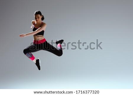 attractive woman in sportswear jumping on grey #1716377320
