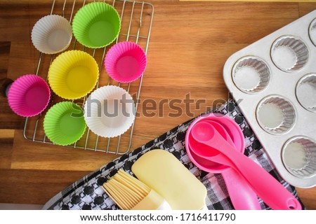 Various kitchen equipments and materials for baking muffines such as silicone cupcake cups, measureng cups, and cupcake pan on a wooden background texture #1716411790