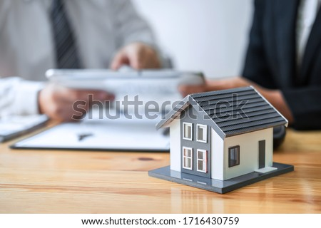 Estate agent are presenting home loan and giving house to client after discussing and signing agreement contract with approved application form, Home Insurance and Real estate investment concept. #1716430759