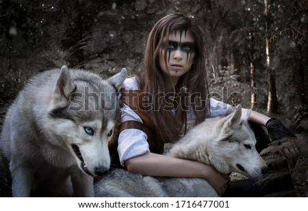 Art photo of a stern hunter with multi-colored eyes and two wolves