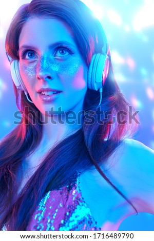 Party and holiday style. Pretty girl with shiny make-up and shiny dress listening to music in headphones and dancing in blue and pink light. #1716489790