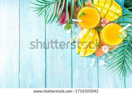Fresh summer tropical fruit drink. Mango smoothie or mango juice, with fresh mango and tropical leaves on outdoor wooden background. Copy space top view. #1716505042