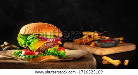 A panorama of a burger with beef, cheese, onion, tomato, and green salad, a side view on a dark background with pickles and French fries, with a place for text #1716525109