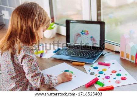 Beautiful toddler girl molding colorful clay cloud with rain watching online learning lesson on the laptop indoor. Distance home learning concept. #1716525403