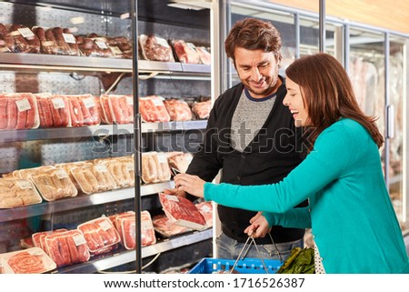 Young couple buying meat scans the label of a packaging in the supermarket