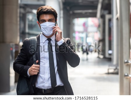 Businessman walking in city with very small amount of people during covid-19 outbreak make phone call and wearing white mask #1716528115