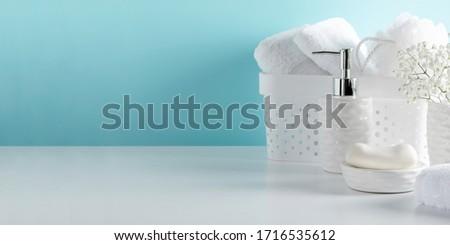 Soft light bathroom decor in pastel blue color, towel, soap dispenser, white flowers, accessories on white wood shelf. Elegant decor bathroom interior. #1716535612