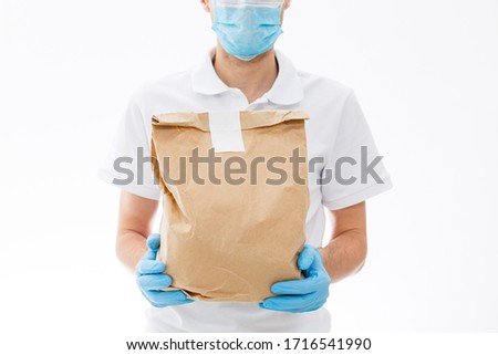 Courier in protective mask and medical gloves delivers takeaway food. Delivery service under quarantine, disease outbreak, coronavirus covid-19 pandemic conditions. #1716541990