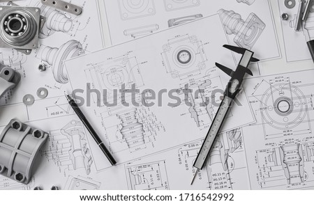 Engineer technician designing drawings mechanicalparts engineering Engine manufacturing factory Industry Industrial work project blueprints measuring bearings caliper tool. #1716542992