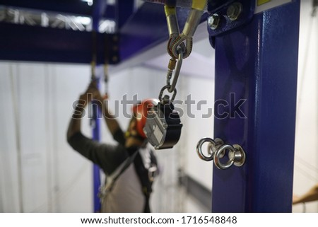 Pictures of stainless steel anchor point on structure pole with defocused abseiler using an inertia reel shock absorber lanyard as fall arrest fall restraint system while working at heights  Royalty-Free Stock Photo #1716548848