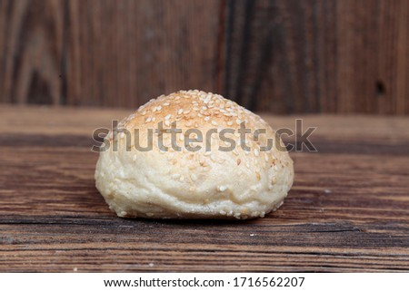 Fresh, homemade, delicious, crunchy bread roll with white sesame seeds. Natural, tasty, freshly baked batch on a brown, wooden, rustic table. Close-up view. #1716562207