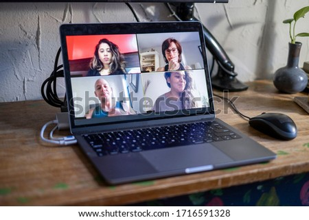 People doing a virtual meeting online.  Laptop on work from home desk.  Coworkers in a team meeting during COVID-19 coronavirus pandemic. #1716591328
