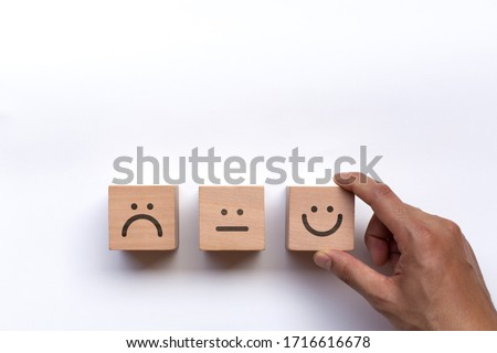 Hand of client show a feedback with smile face wood cube. Service rating, satisfaction concept #1716616678