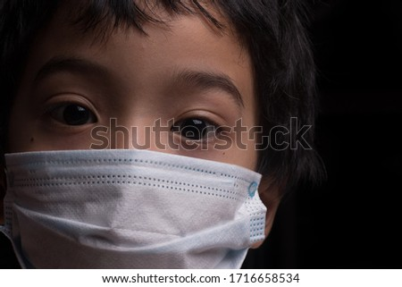 A child wearing a medical face mask isolated over dark background #1716658534