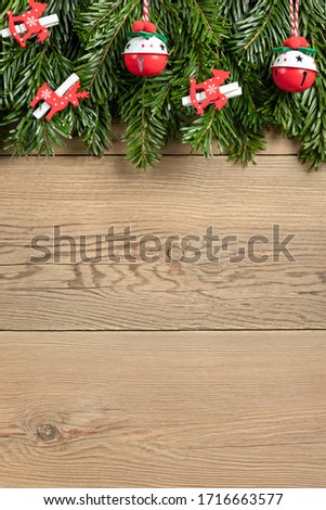 Christmas tree branches with red decorations on a wooden wall background. Template for greeting card or design. Virtical banner with copy space