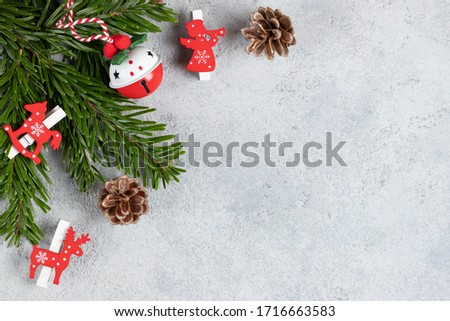 Christmas tree branches with red decorations on a gray table. Template for greeting card or design. Horizontal banner with copy space