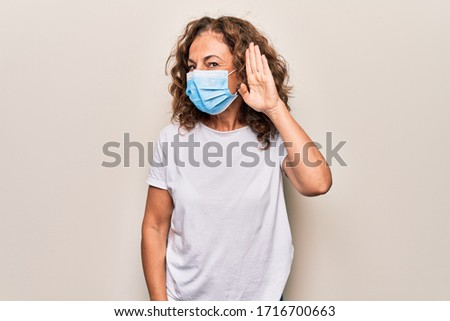 Middle age woman wearing coronavirus protection mask for covid-19 epidemic virus smiling with hand over ear listening and hearing to rumor or gossip. Deafness concept. #1716700663