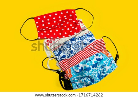 Isolated Group of Home Made, Hand Made,Sewing Colorful Nice Face, Protective Masks on a Yellow Background. Cheerful Cotton Masks as a protections against Corona Virus, Covid 19 Royalty-Free Stock Photo #1716714262