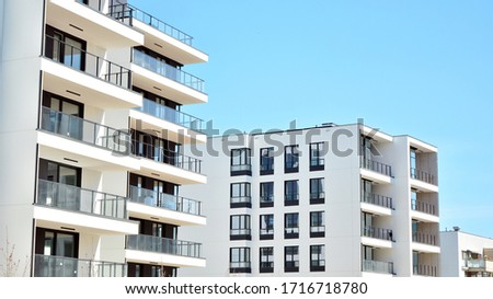 Contemporary residential building exterior in the daylight. Modern apartment buildings on a sunny day with a blue sky. Facade of a modern apartment building #1716718780