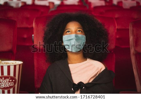 Happy african kid wearing protective face mask and watching movie in theater/theatre cinema protect infection from coronavirus covid-19, social distancing in theater concept #1716728401