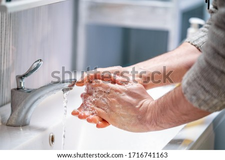 man washes his hands with soap at home. concept virus protection. hand hygiene. #1716741163